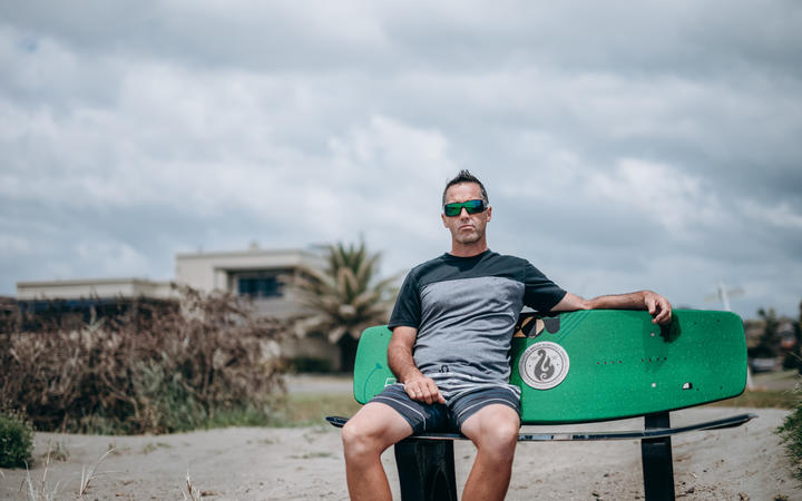 Mark Inman sit on a surfboard bench in memory of his brother tour guide Hayden Marshall-Inman whose body has not been recovered since the Whakaari White Island eruption.