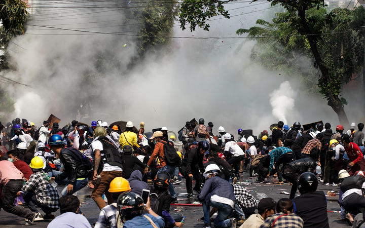 Protesters react after police fired tear gas during a demonstration against the military coup in Mandalay on 3 March
