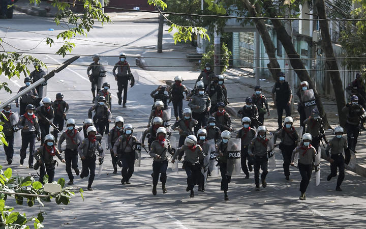 Police run towards protesters to disperse a demonstration being held against the military coup in Yangon on 3 March