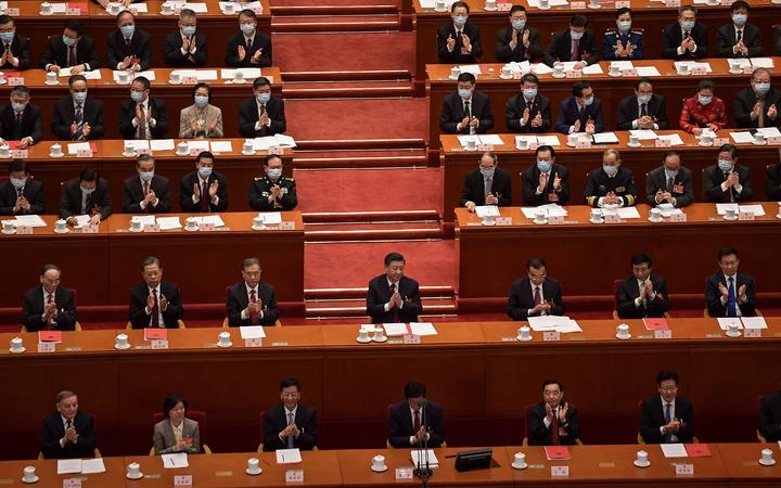 China's President Xi Jinping (centre) applauds with other leaders after the result of the vote on changes to Hong Kong's election system was announced in a session of the National People's Congress on Thursday.