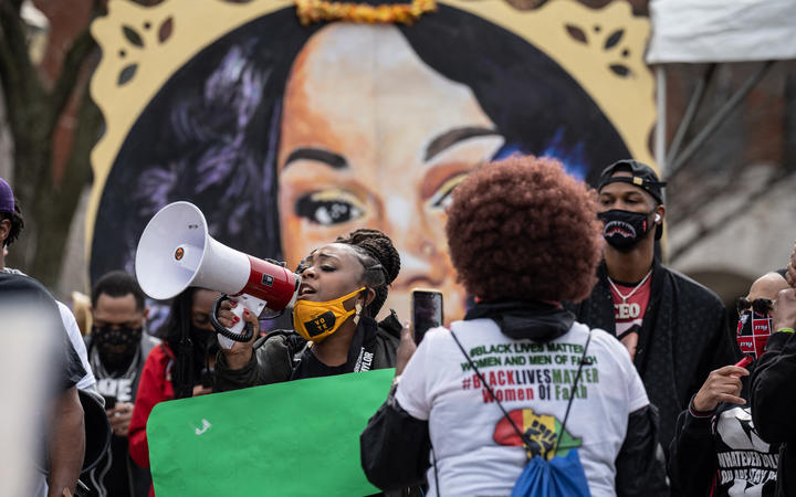 A woman shouts through a megaphone during a protest memorial for Breonna Taylor in Jefferson Square Park, Louisville, Kentucky.