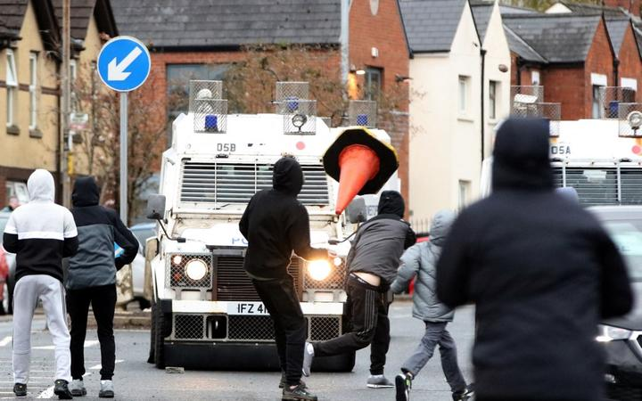 Nationalist youths attack police officers in the Springfield Road area of Belfast on April 8, 2021 as disorder continued in the Northern Ireland capital following days of mainly loyalist violence. -