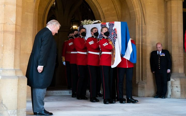 Pallbearers carry the coffin of Britain's Prince Philip, Duke of Edinburgh draped with his Personal Standard to the purpose built Land Rover Defender for the ceremonial funeral procession to St George's Chapel in Windsor Castle in Windsor, west of London, on April 17, 2021.