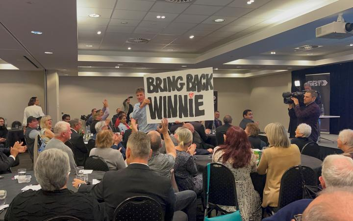 A person in the crowd puts up a poster in support of New Zealand First leader Winston Peters at the party's AGM on 20 June, 2021.