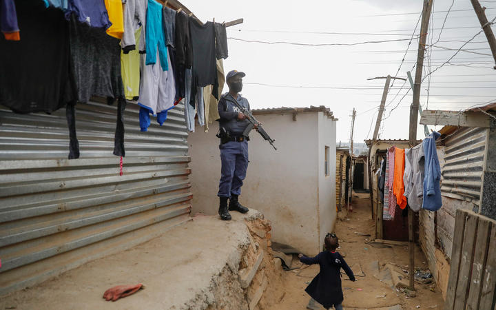 A child runs past a member of the South African Police Services (SAPS) while keeping watch during a joint operation with South African Defence Force (SANDF) to recover stolen goods from the looting in Alexandra township, Johannesburg, on July 16, 2021. -