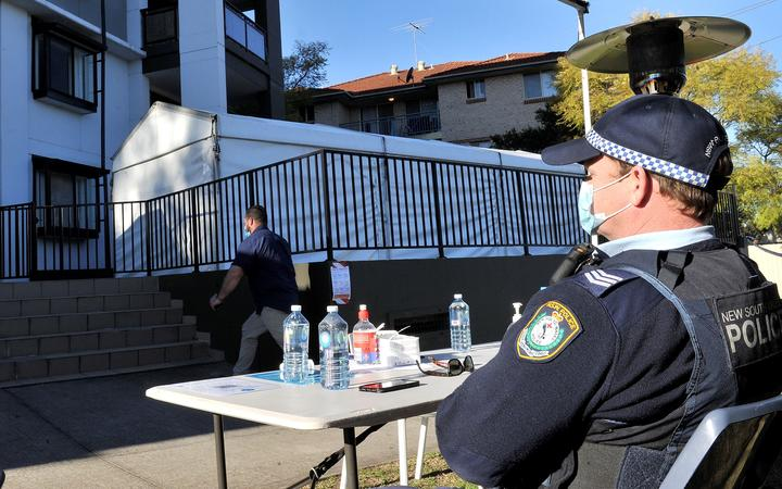 A police officer stays guard outside an isolated residential building in Sydney's western suburb of Blacktown after several cases were reported among the residents.