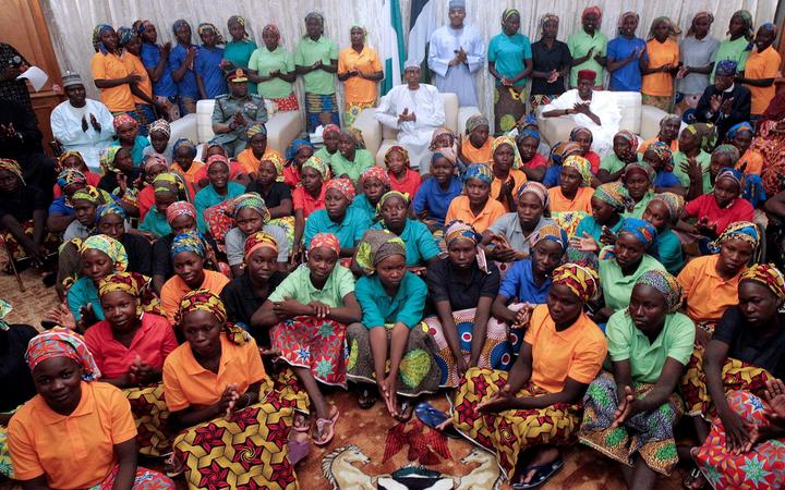 An handout picture released by the PGDBA&HND Mass Communication shows Nigeria's President Muhammadu Buhari (C) sitting among the 82 rescued Chibok girls during a reception ceremony at the Presidential Villa in Abuja, on May 7, 2017.
