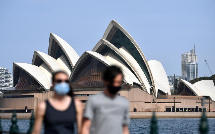 People wearing face masks walk in front of the Opera House in Sydney, New South Wales.