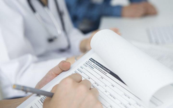 Doctor, nurse of other health worker filling out medical form
