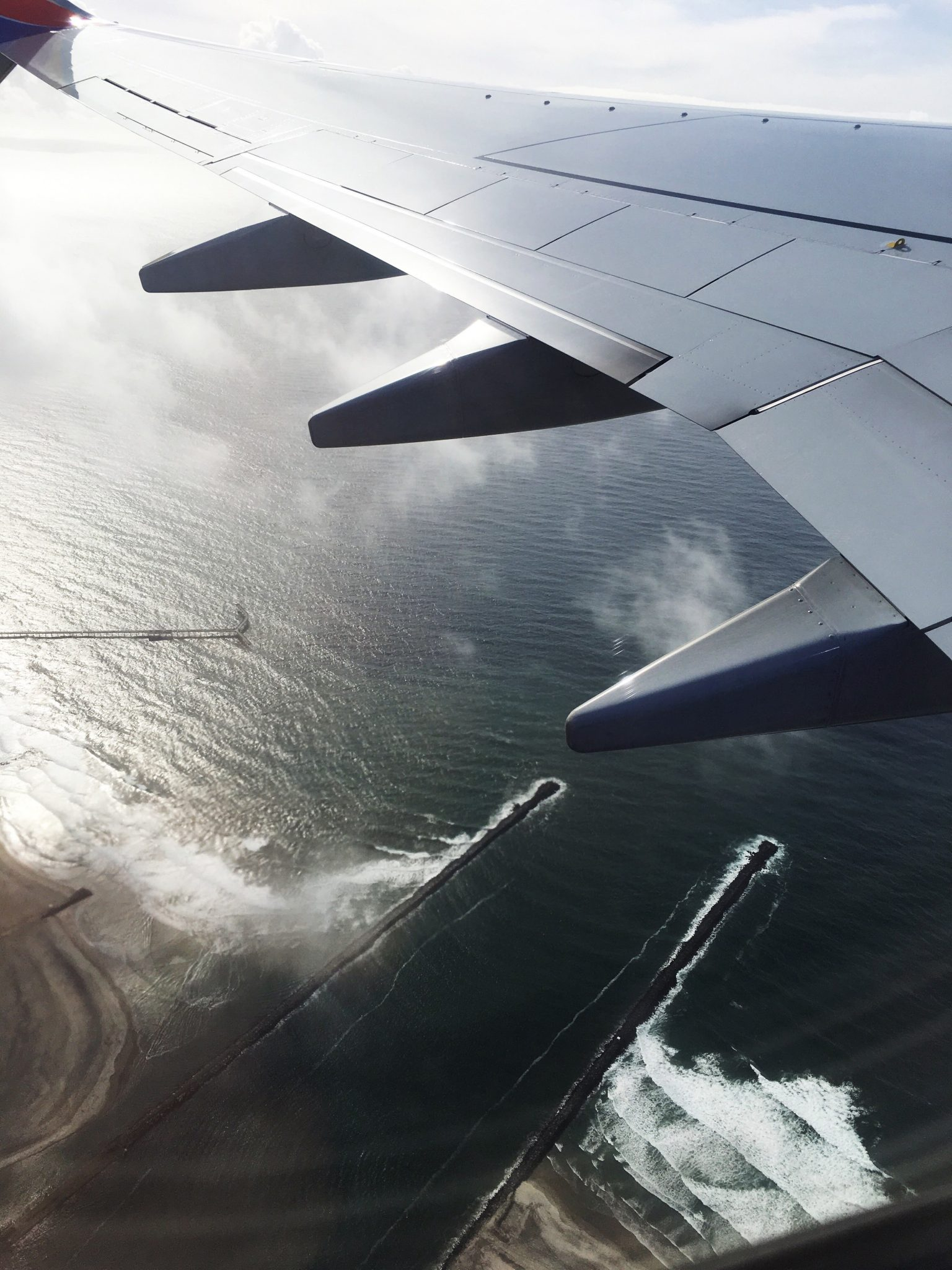 Travel - Captured plane wing, flying over the Pacific Ocean near San Diego, California