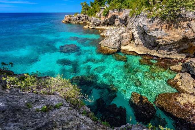 Beautiful clear turquoise water near rocks and cliffs in Negril Jamaica