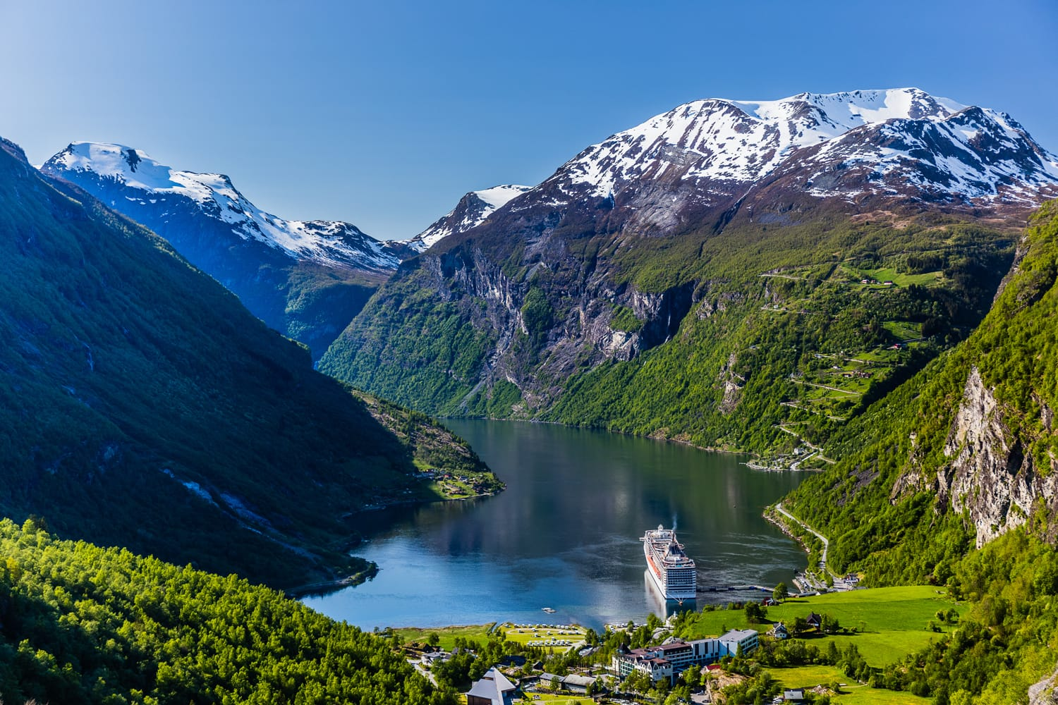 Geirangerfjord with a ship in a port from above, with mountain peaks covered with snow