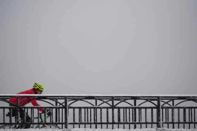 bicyclist riding in cold, snowy, winter weather