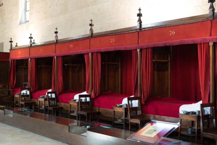 Lined up beds in the Grand Hall of the Hospices of Beaune, Burgundy - France - www.RoadTripsaroundtheWorld.com
