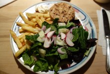 Veggie burger with baked fries and a salad