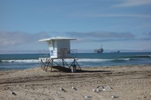 A life guard station and oil platform share the same photo