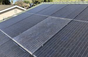 Picture of many solar panels but one panel is broken and not producing power.