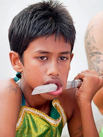 Knife in boys mouth at the bizarre Vegetarian Festival, Phuket, Thailand