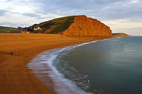 A lone fisherman stands on the beach at West Bay, Jurassic Coast, UNESCO World Heritage Site, Dorset, England, United Kingdom, Europe