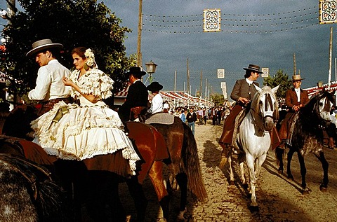 People in traditional costumes on horseback under thunderclouds, Feria de Abril, Sevilla, Andalusia, Spain, Europe