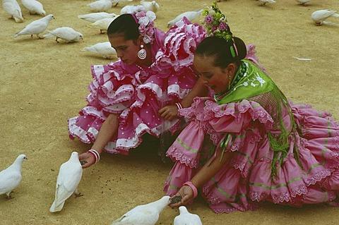Girls feeding doves, Feria de Abril, Sevilla, Andalusia, Spain