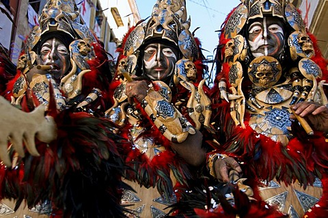 Men dressed in elaborate costumes, loosely representing North African tribes, the Moors, smoke cigars while marching in a parade during the Festival of Moors and Christians, (La Fiesta de Moros y Cristianos) in the old town of Alcoy, Alicante Province.