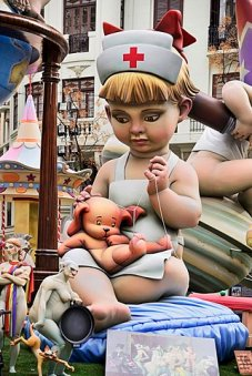 Spain, Valencia Province, Valencia, Papier Mache figure of young girl in nurses outfit with teddy bear in the street during Las Fallas festival.
