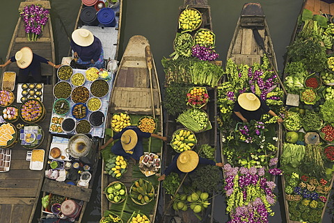 Aerial view of a floating market on a canal in Bangkok, local boats laden with fresh food, moored close together