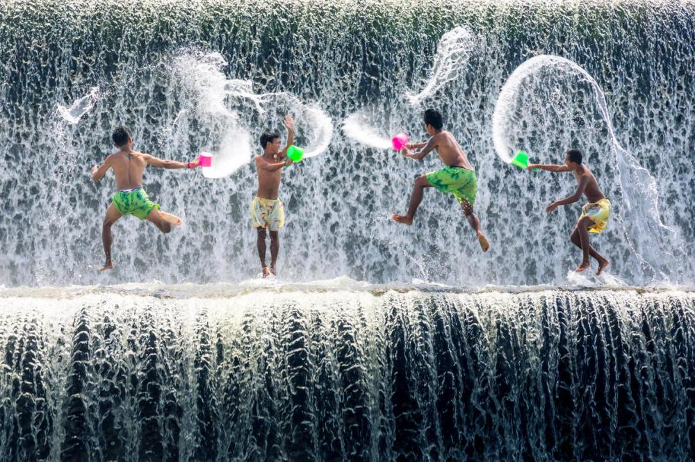 Boys playing in a waterfall image