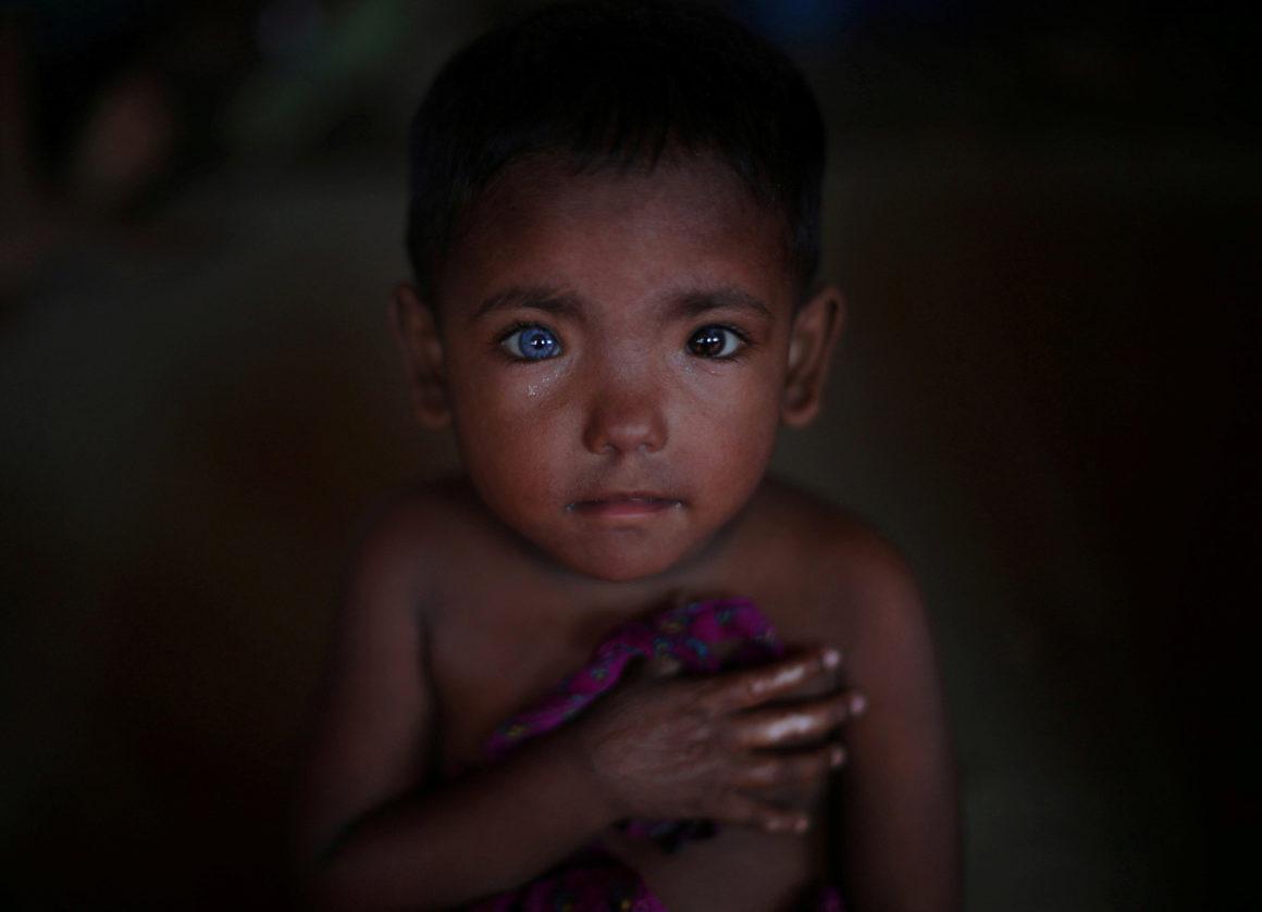 5 novembre 2017 - Hosne Ara, 4 anni, un rifugiato rohingya fuggito dal Myanmar, ascolta i bambini che cantano nel campo profughi di Kutupalong, in Bangladesh. (Hannah McKay, Reuters)