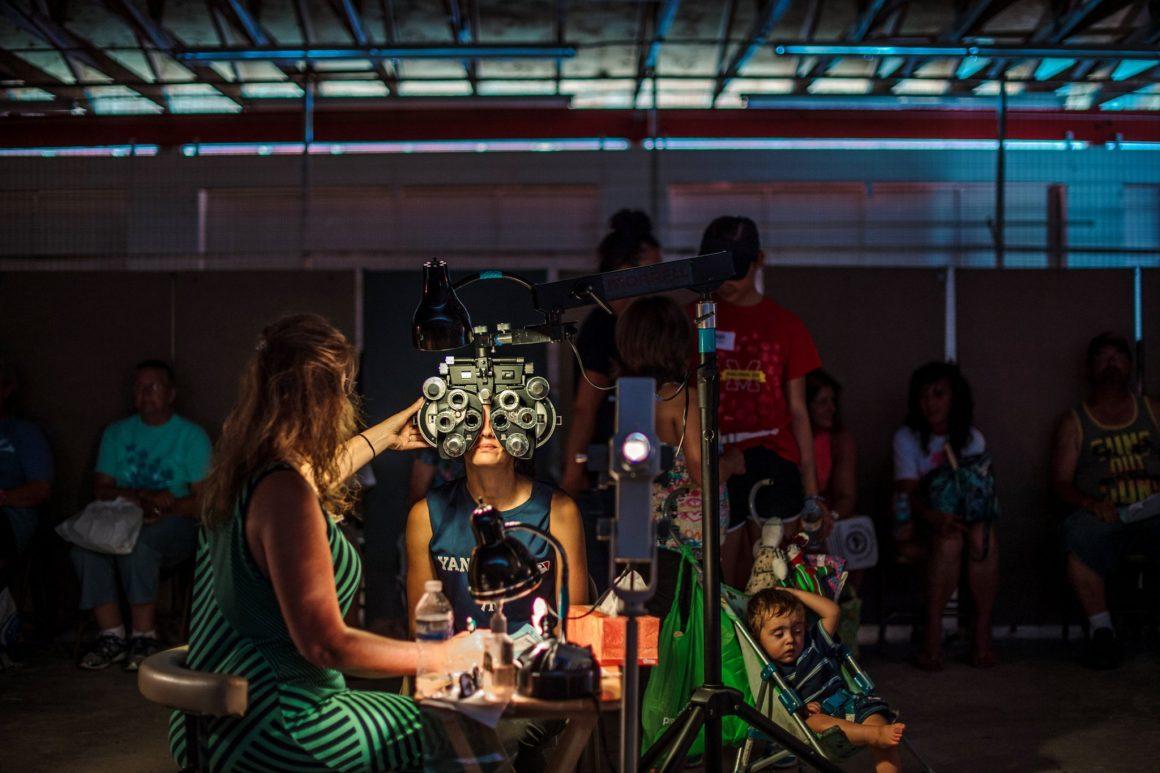 21 luglio 2017 - A Wise, in Virginia, un optometrista volontario al lavoro presso la più grande clinica sanitaria gratuita pop-up della nazione, che ha attirato più di 2000 persone in una fiera in Appalachia. (Foto di Mike Belleme per il The New York Times)