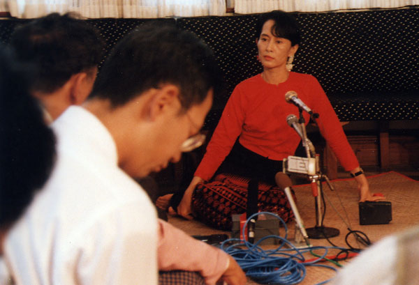 Photographed at a press conference in her home, September 1996, after a government crackdown on her party. By flickr user taptaptap