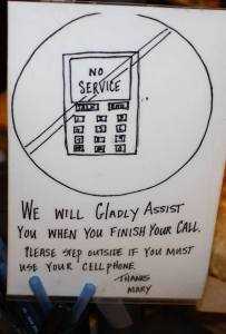 Sign at register asking people to NOT use their cell phone at Bread and Roses In Ogunquit, Maine.  Their coffee and pastries are awesome too!