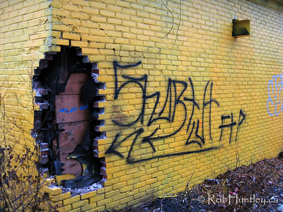 Graffiti leads the eye to the hole in the wall. The brick layer and tar paper has been ripped out of the corner of this brightly painted house.