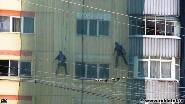 O meserie grea din mai multe meserii grele: alpiniști utilitari zugrăvind pereții exteriori ai unei clădiri