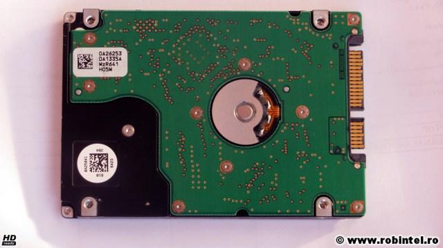 Hard diskul Hitachi HTS721080 văzut de pe verso. Conectorul SATA este acum în partea stângă. Se observă lucrătura roboților, cu poziționarea aproape rotundă a unor găuri de traversare, semn distinctiv că la fabricarea acestuia s-au folosit roboți industriali de mare precizie.