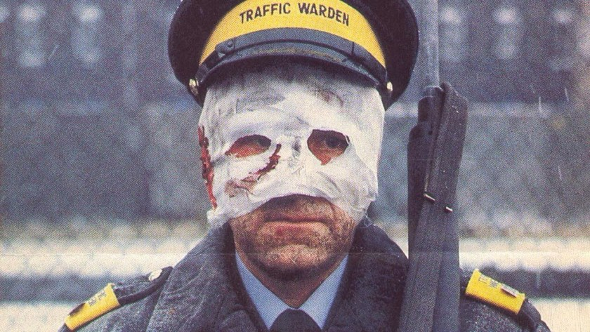 man in uniform with burns mask