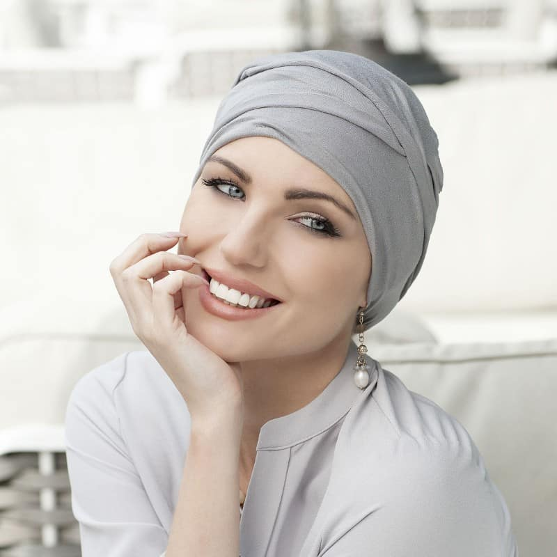 Woman with no hair wearing a grey bamboo hat.