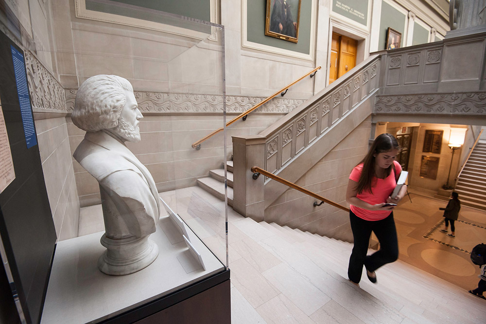 statue of Frederick Douglass in a glass case on the library staircase as people walk past