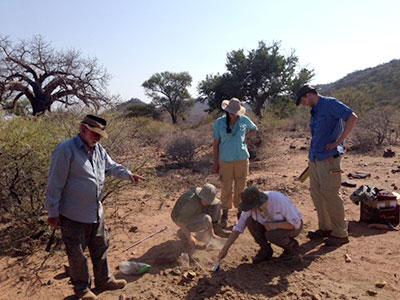 grupo de pesquisadores se reúne em torno de um dispositivo de medição em um grande campo aberto