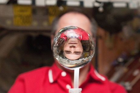 NASA astronaut Kevin Ford watches a water bubble float freely between him and the camera, showing his image refracted, within the Unity node of the International Space Station. Photo: NASA