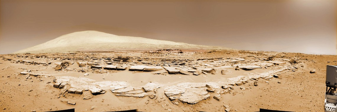Martian landscape scene with rows of striated rocks in the foreground and spectacular Mount Sharp on the horizon. NASA's Curiosity Mars rover paused mid drive at the Junda outcrop to snap the component images for this colorized navcam camera photomosaic on Sol 548 (Feb. 19, 2014) and then continued traveling southwards towards mountain base. Image: NASA/JPL-Caltech/Marco Di Lorenzo/Ken Kremer