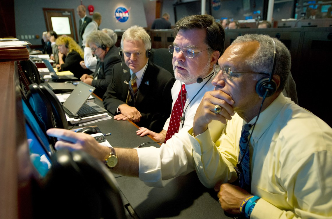 Then NASA Deputy Director of Planetary Division Jim Adams, center, and NASA Administrator Charles Bolden, right, review incoming data during the countdown to launch of the twin GRAIL spacecraft in 2011 at the Cape Canaveral Air Force Station. Credit: NASA/Bill Ingalls