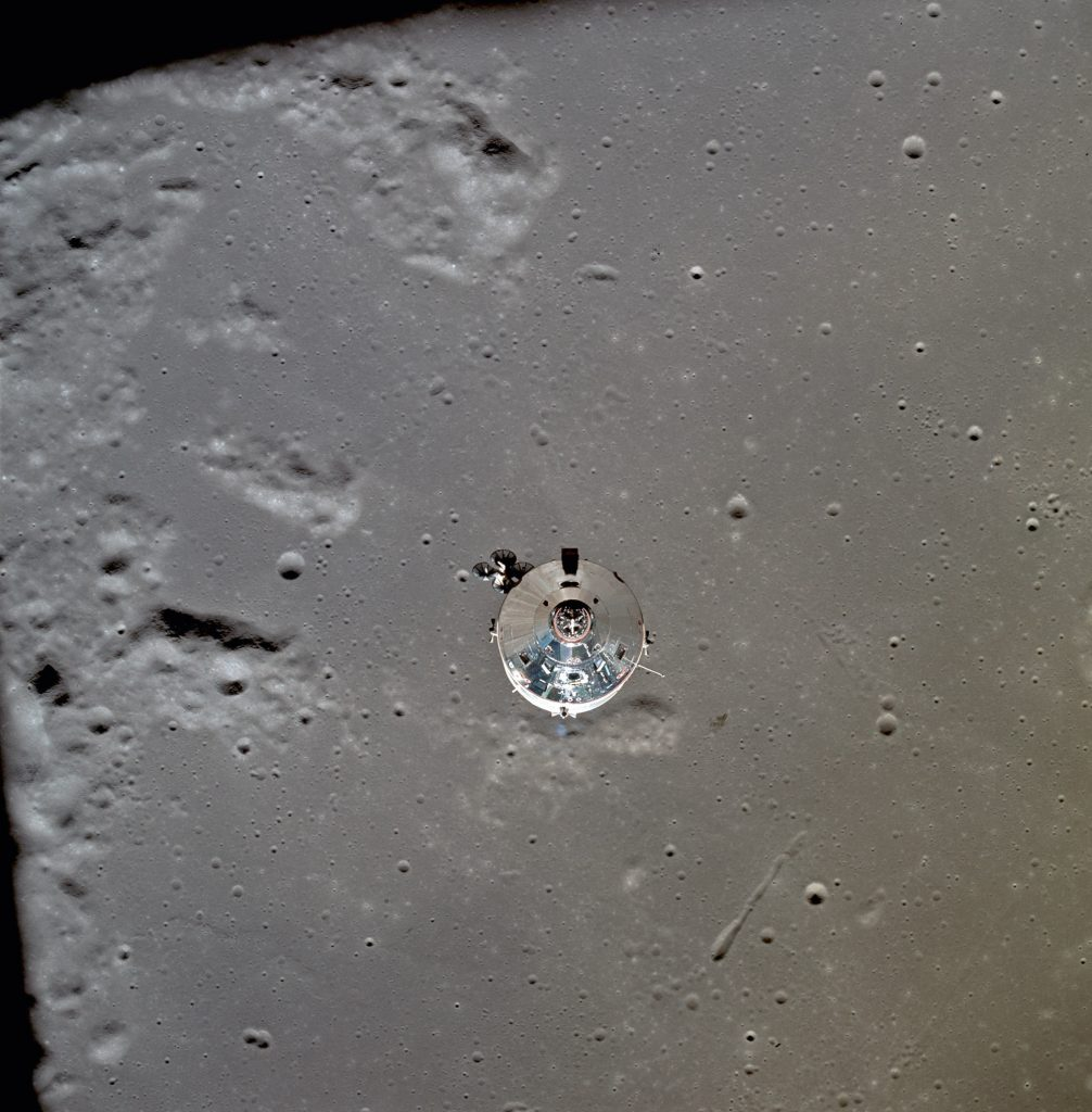 The CM seen orbiting the Moon just after separation of the LM. The lunar surface below is in the north central Sea of Fertility approximately 125 km below the spacecraft..