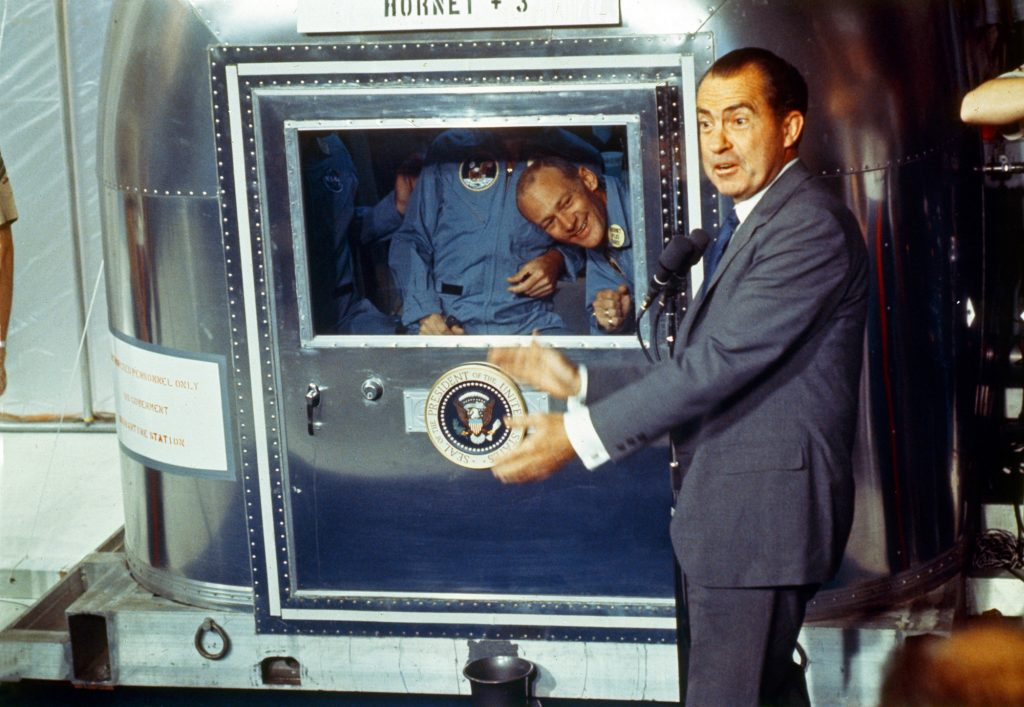 Already confined to the Mobile Quarantine Facility, President Richard Nixon welcomes the Apollo 11 astronauts aboard the U.S.S. Hornet.