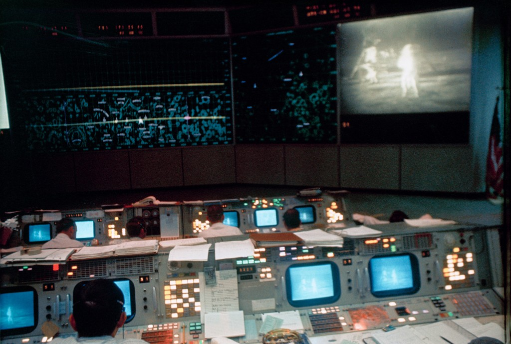 View of NASA Mission Control in Houston, Texas during the lunar surface EVA by Armstrong and Aldrin. The television monitor shows them on the surface of the moon.