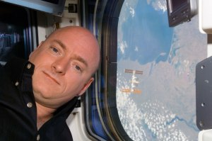 STS-118 Commander CDR Scott Kelly posing for a photo near a window on the Space Shuttle Endeavour. The International Space Station ISS is visible behind him. Credit: NASA