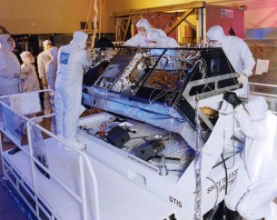 Engineers in a clean room at Ball Aerospace in Boulder, Colo., work on one of Hubble's instruments, the Space Telescope Imaging Spectrograph (STIS). The instrument, installed in Hubble in 1997, breaks light into colors, giving scientists an important analytical tool for studying the cosmos. STIS has been used to study such objects as black holes, new stars, and massive planets forming outside our solar system.