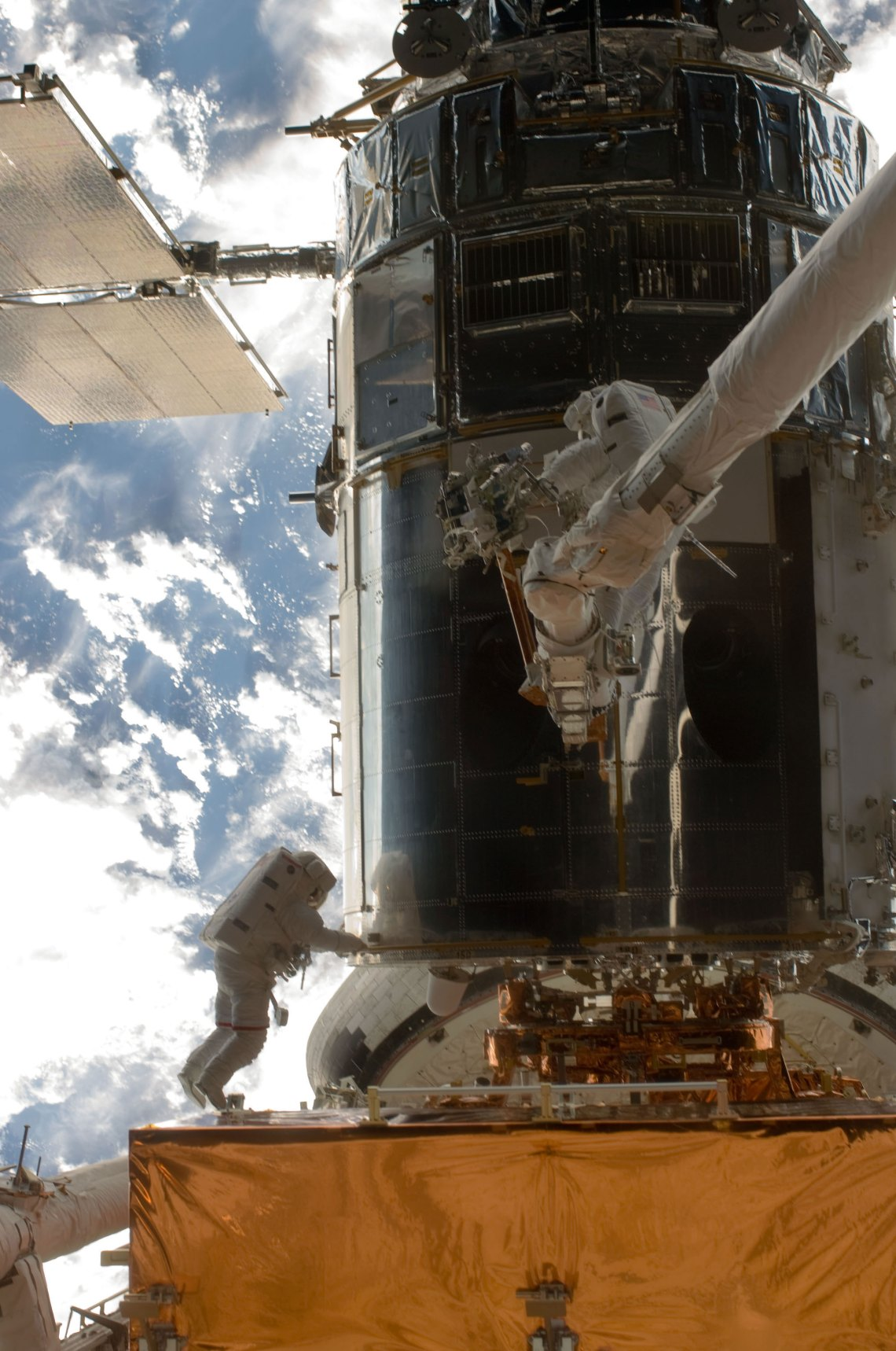 John Grunsfeld and  Andrew Feustel, perched  alone on the end  of the Atlantis'  RMS arm, conduct the first  of five STS-125 spacewalks  to repair and upgrade the  Hubble Space Telescope,  temporarily locked down  in the cargo bay of the  Earth-orbiting shuttle.   Credit: NASA