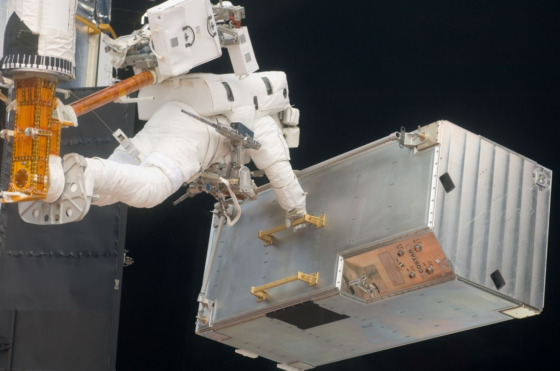 Andrew Feustel, positioned on a foot restraint on the end of Atlantis' remote manipulator system (RMS), moves the Corrective Optics Space Telescope Axial Replacement (COSTAR) during the mission's third EVA session to refurbish and upgrade the Hubble Space Telescope.  Credit: NASA